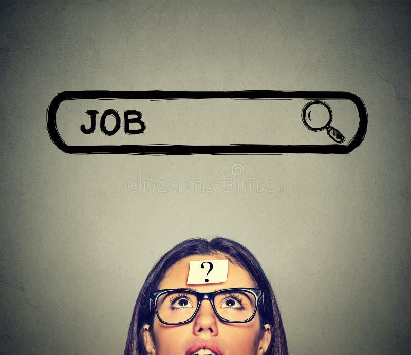 Женщина в стеклах думая ищущ новая работа изолированная на серой предпосылке стены стоковое фото