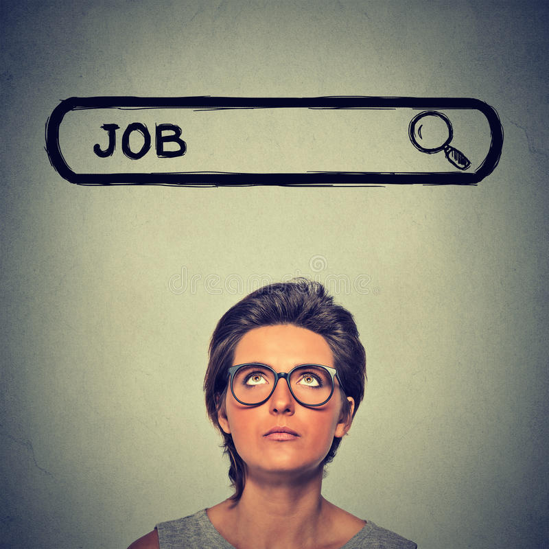 Женщина в стеклах думая ищущ новая работа изолированная на серой предпосылке стены стоковые изображения