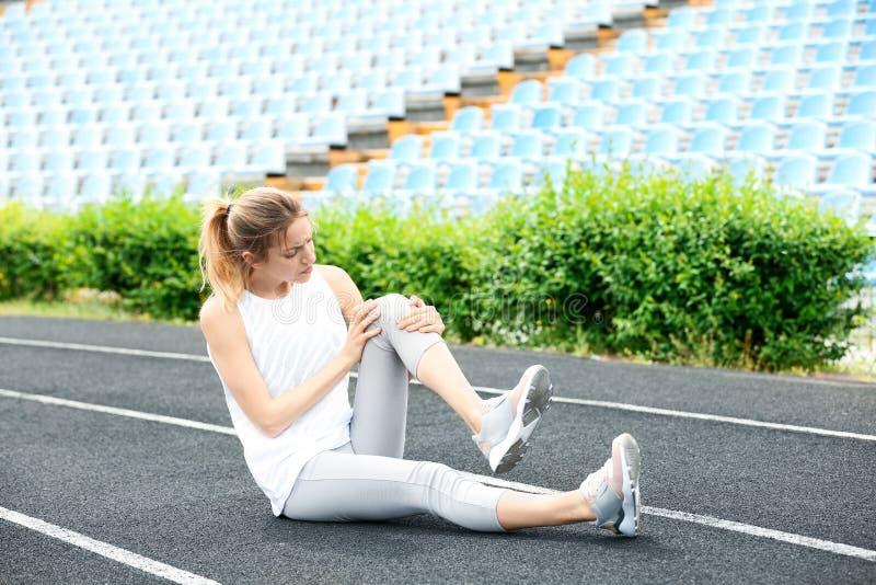 Женщина в страдании sportswear от боли колена стоковые фото