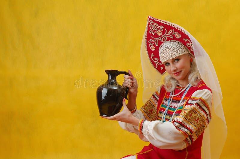 Женщина в фольклорном русском платье держит кувшин стоковое фото