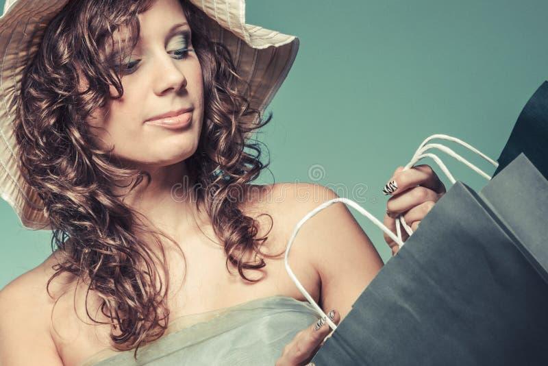 Женщина в хозяйственной сумке владением платья и шляпы стоковое фото rf
