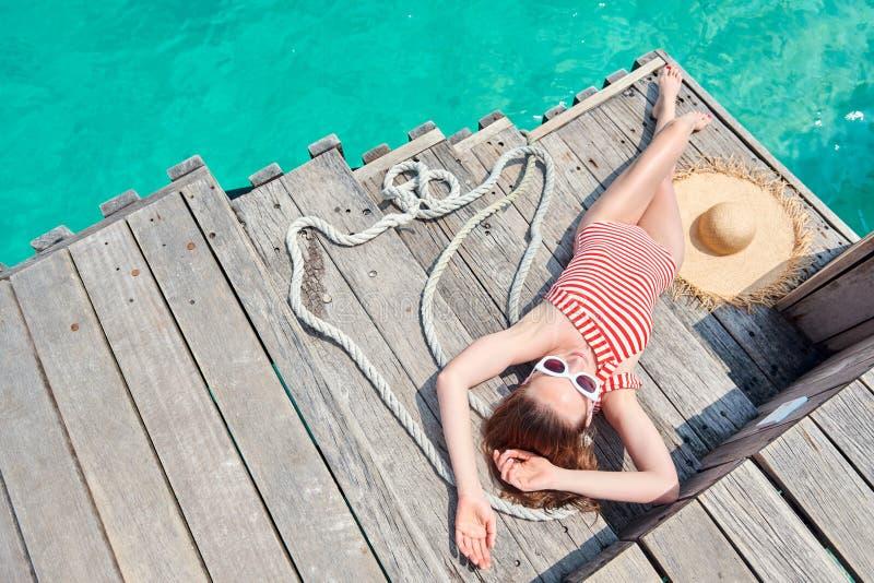 Женщина в цельном купальнике на деревянной моле стоковая фотография