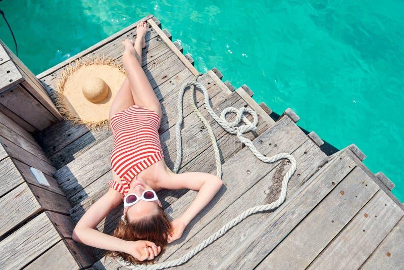 Женщина в цельном купальнике на деревянной моле стоковые изображения rf