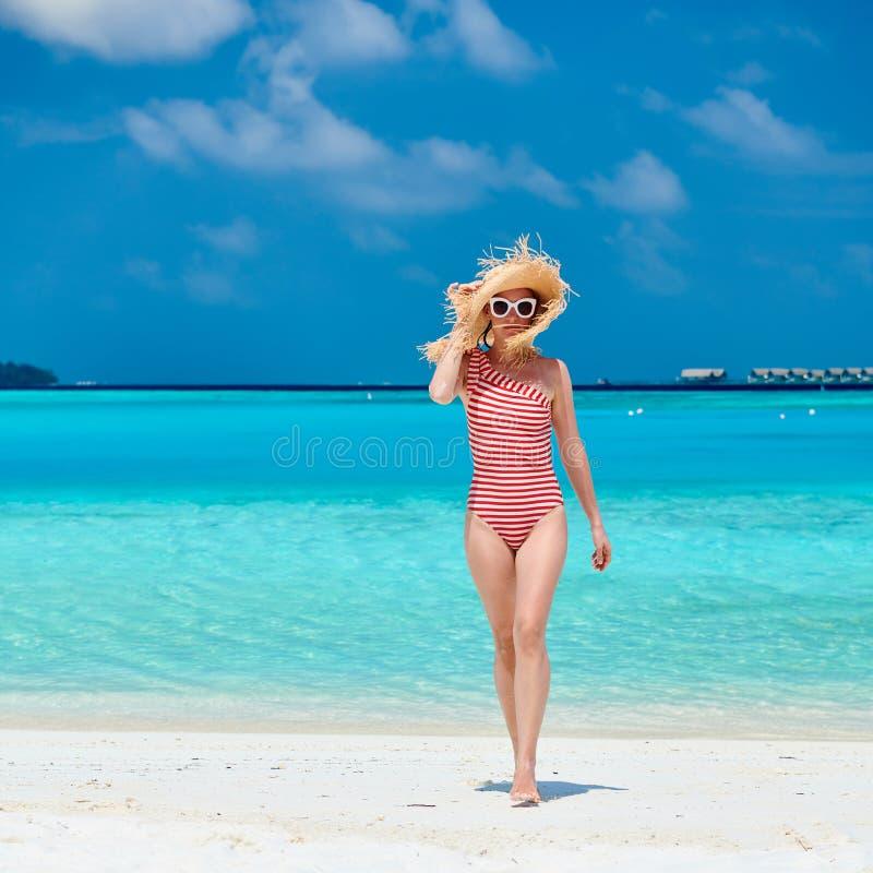 Женщина в цельном купальнике на пляже стоковые изображения