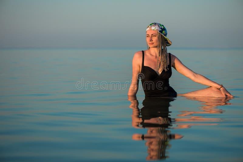 Женщина в черном костюме заплыва ослабляя в море стоковая фотография