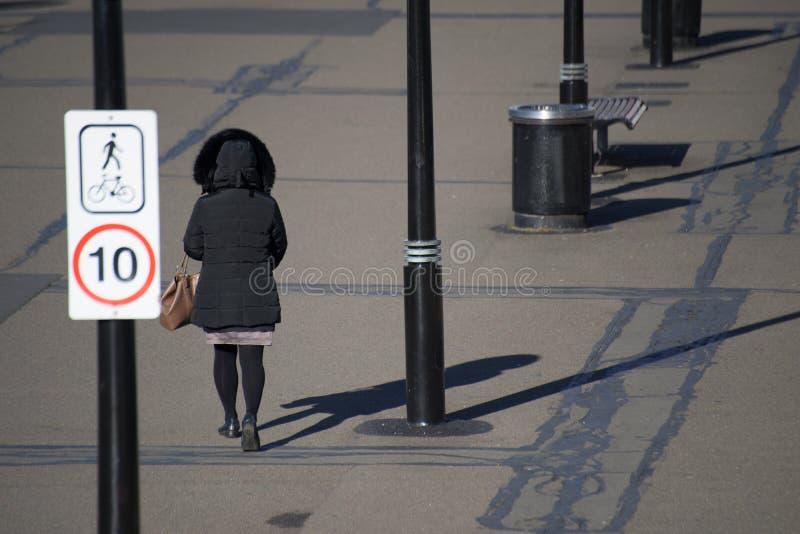 Женщина в черном пальто куртки идя от зада стоковая фотография