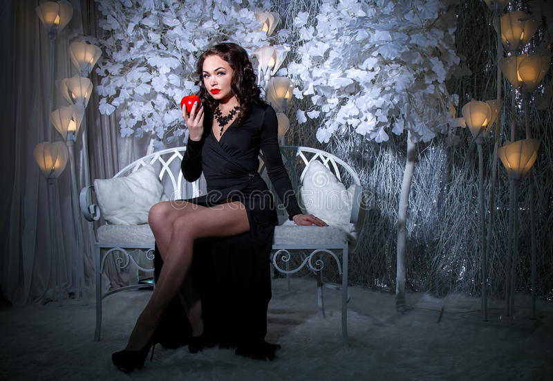 Женщина в черном платье в снеге покрыла парк стоковое фото rf