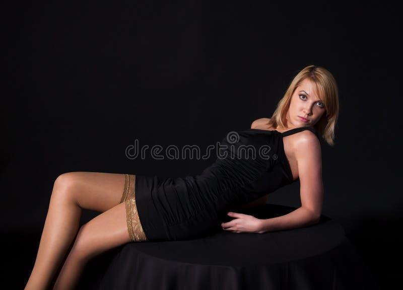 Женщина в черном платье над темной предпосылкой стоковые фото