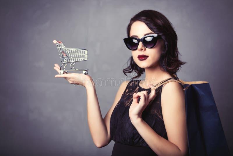 Женщина в черном платье с магазинной тележкаой и сумкой стоковые изображения