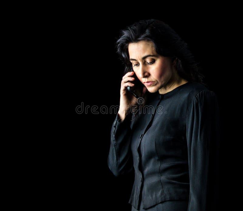Женщина в черноте используя сотовый телефон стоковая фотография