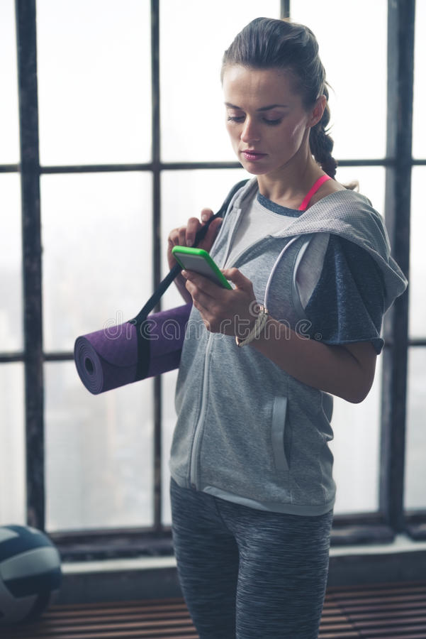 Женщина в шестерне разминки в спортзале просторной квартиры проверяя мобильный телефон стоковое фото rf