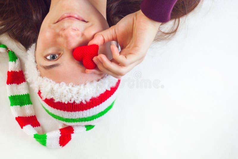 Женщина в шляпе крышки рождества Санта Клауса держа красное сердце в nahd и усмехаться стоковые изображения rf