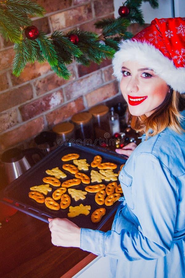 Женщина в шляпе Санта Клауса с подносом выпечки стоковая фотография