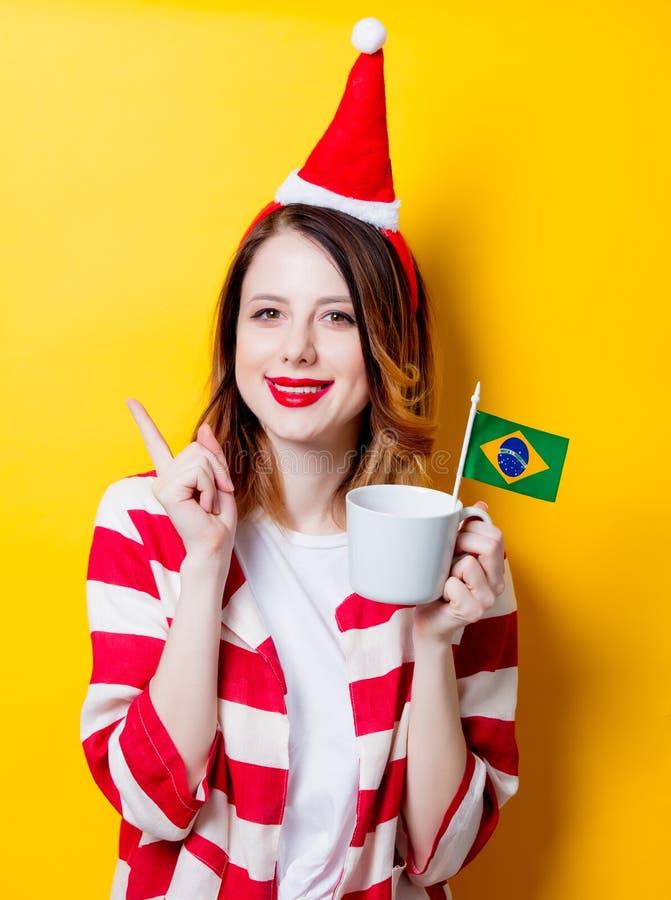 Женщина в шляпе Санта Клауса с флагом и чашкой Бразилии стоковые фото