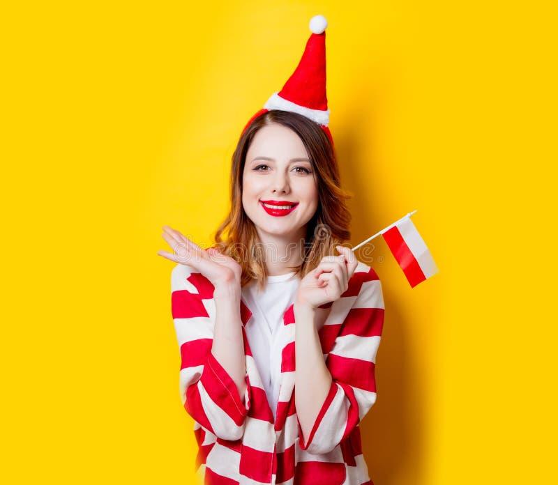 Женщина в шляпе Санта Клауса с флагом Польши стоковое фото rf