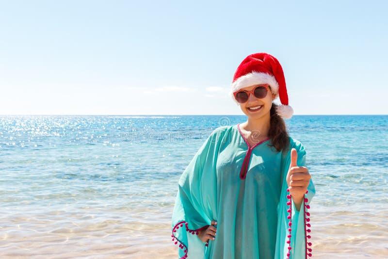 Женщина в шляпе ` s santa в бикини на тропическом пляже рождество соединило пустое специально изображение офиса компьтер-книжки и стоковая фотография