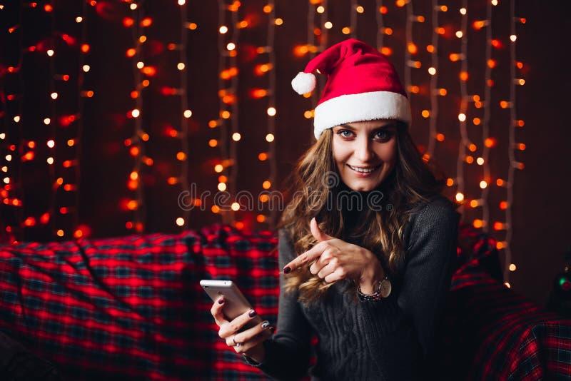 Женщина в шляпе santa указывая пальцем на умный телефон стоковое изображение rf