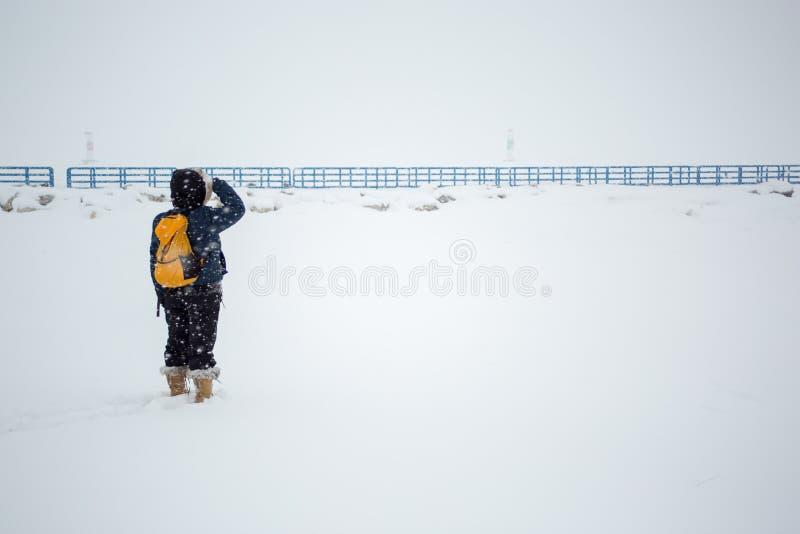 Женщина в шторме снега с голубыми перилами стоковое фото
