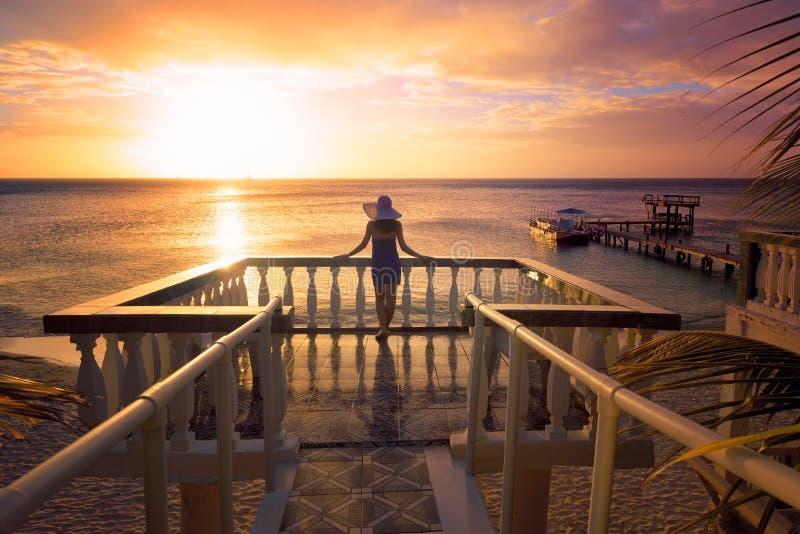 Женщина в шляпе смотря романтичный карибский заход солнца стоковые изображения rf