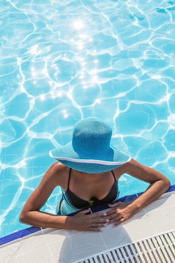 Женщина в шляпе солнца в бассейне Взгляд сверху стоковые изображения