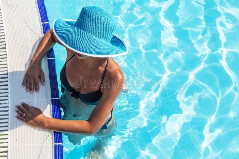 Женщина в шляпе солнца в бассейне Взгляд сверху стоковые фотографии rf