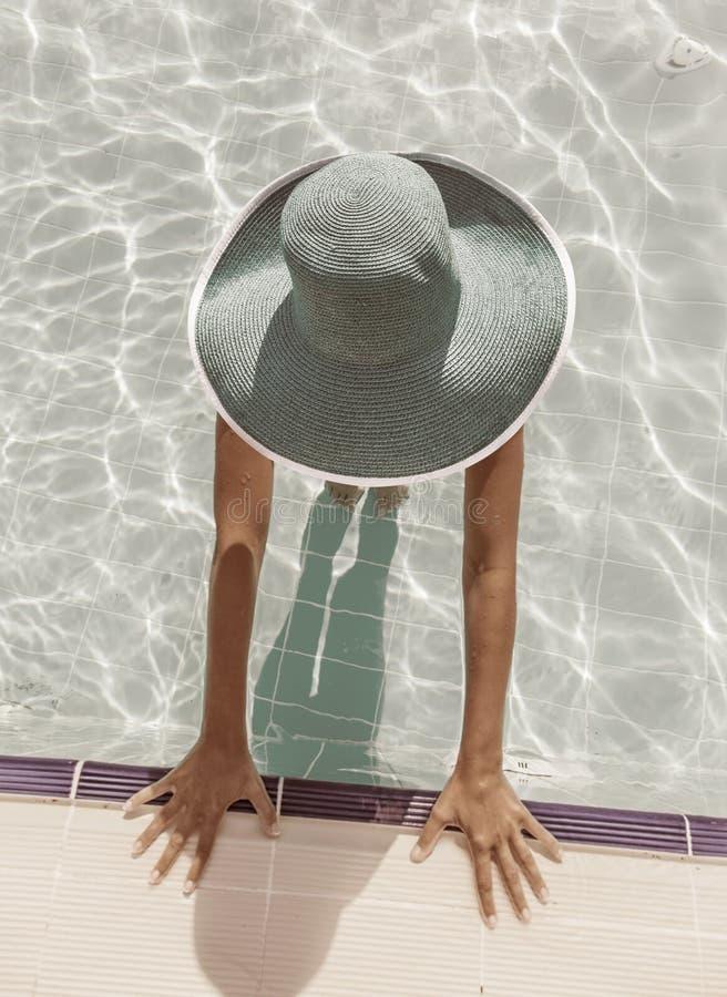 Женщина в шляпе солнца в бассейне Взгляд сверху стоковое изображение