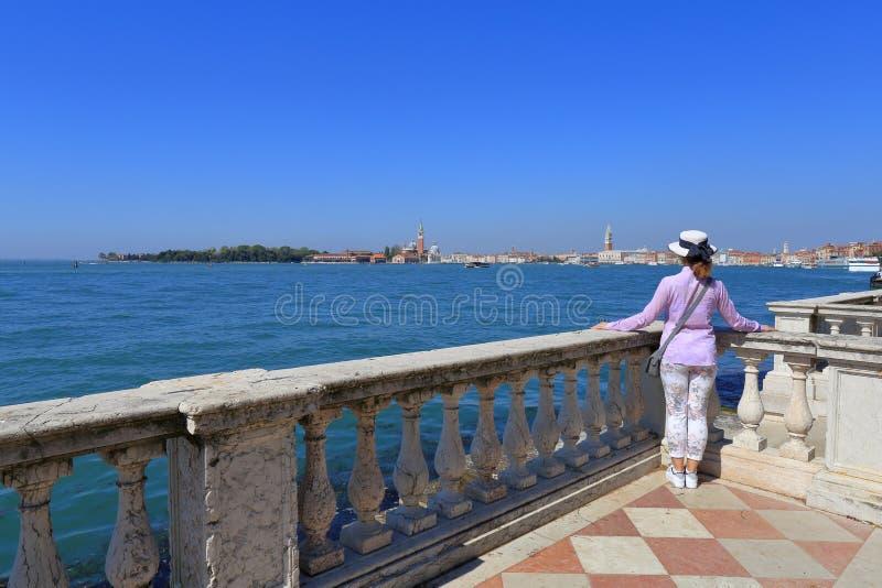 Женщина в шляпе стоит склонность на балюстраде и смотрит город Венеции стоковое изображение rf