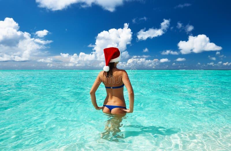 Женщина в шляпе santa на пляже стоковое изображение