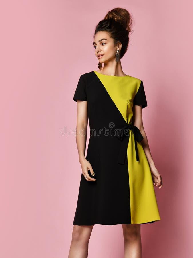 Женщина в элегантном черном платье коктейля стоит полностью рост и смотрит прочь на розовой предпосылке стоковые фото