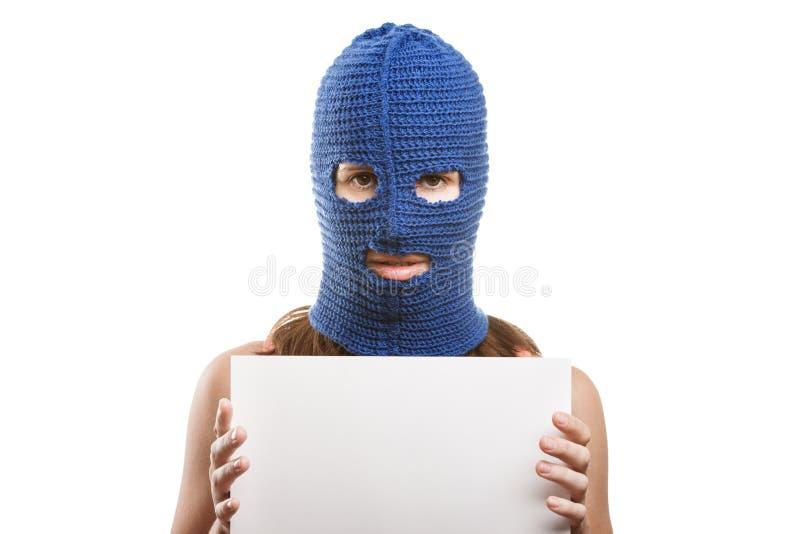 Женщина в balaclava держа пустую карточку стоковые фото