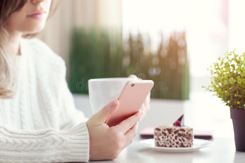 Женщина в caffee и держать кафа выпивая розовый телефон стоковые фото