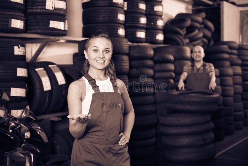 Женщина в coveralls работы работая в автоматическом сервисном центре стоковое изображение