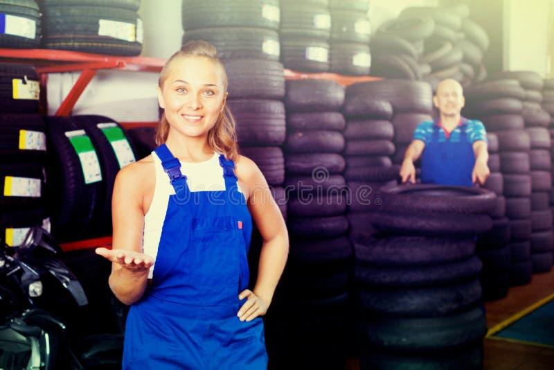 Женщина в coveralls работы работая в автоматическом сервисном центре стоковое фото