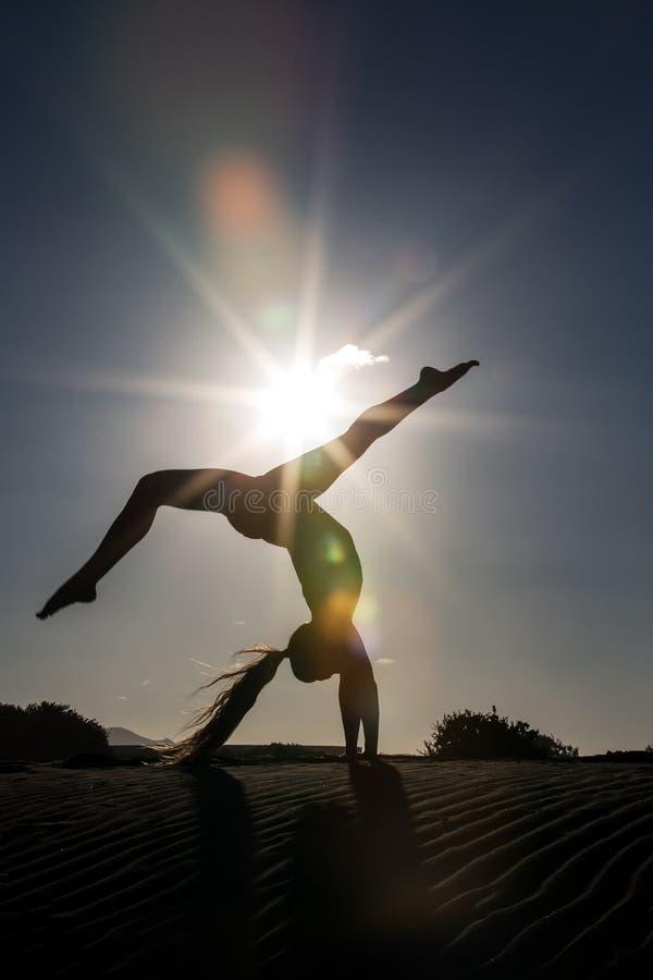 Женщина в handstand на пляже стоковое изображение rf