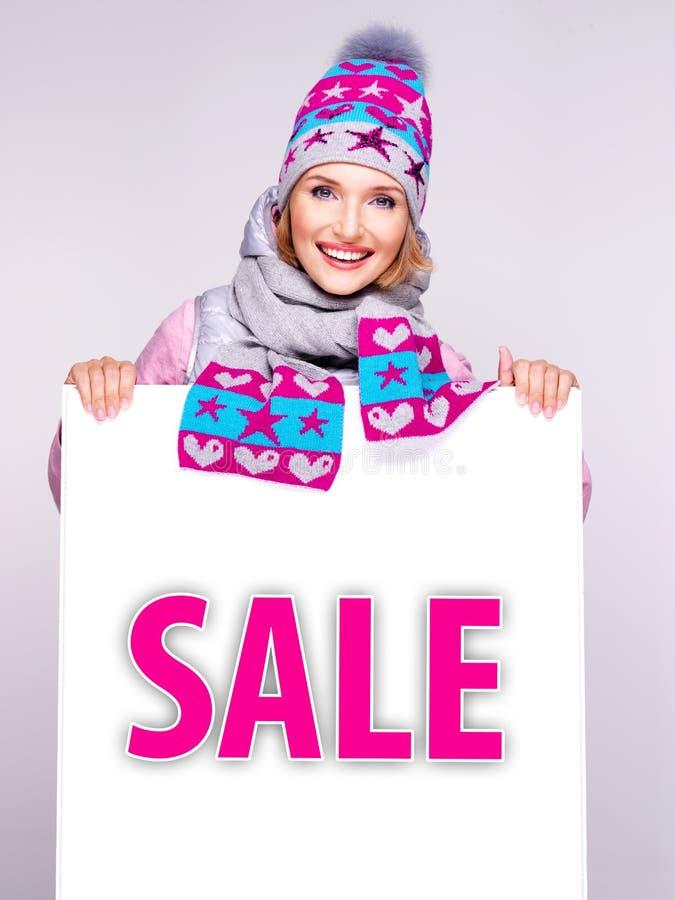 Женщина в outerwear зимы держит белое знамя с словом продажи стоковое фото rf