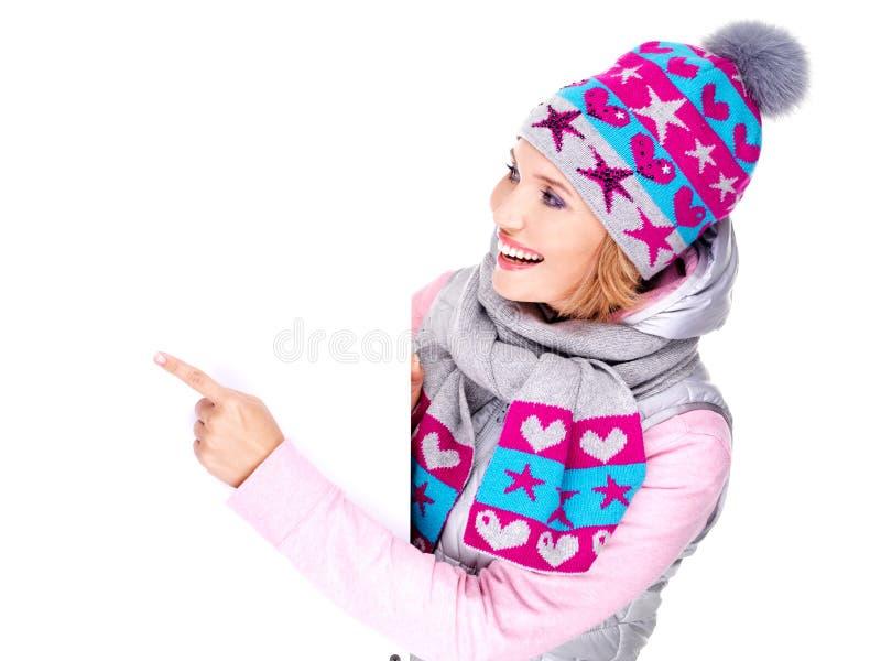 Женщина в outerwear зимы держит знамя и пункты на ей стоковая фотография
