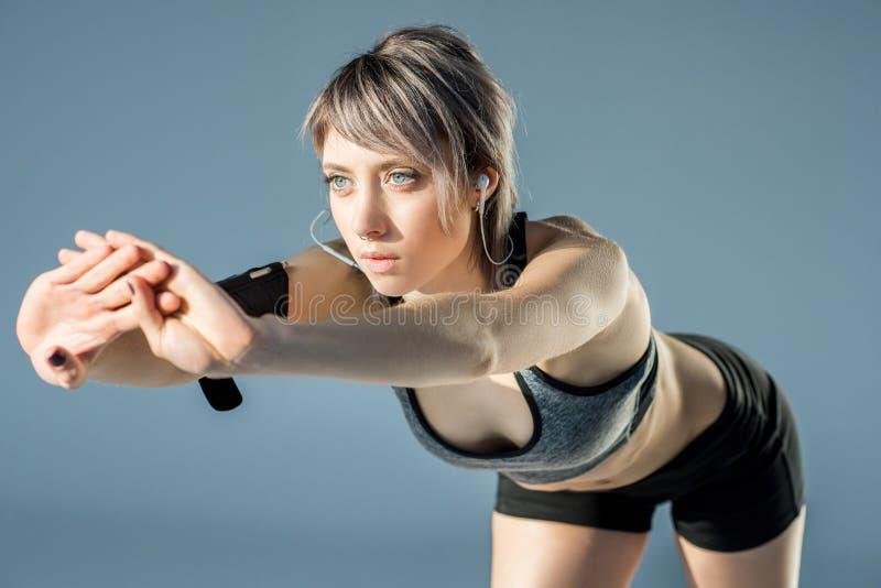 Женщина в sportive одеждах с протягивать наушников стоковое фото