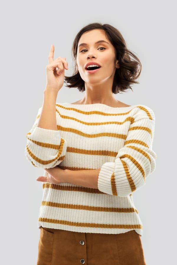 Женщина в striped пуловере указывая ее палец вверх стоковые изображения rf