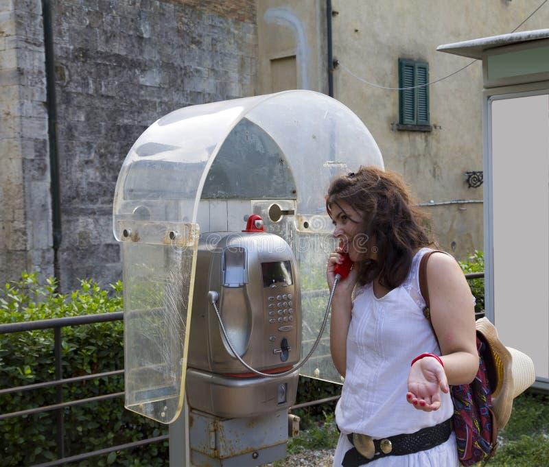 Женщина говоря в телефонной будке стоковое фото