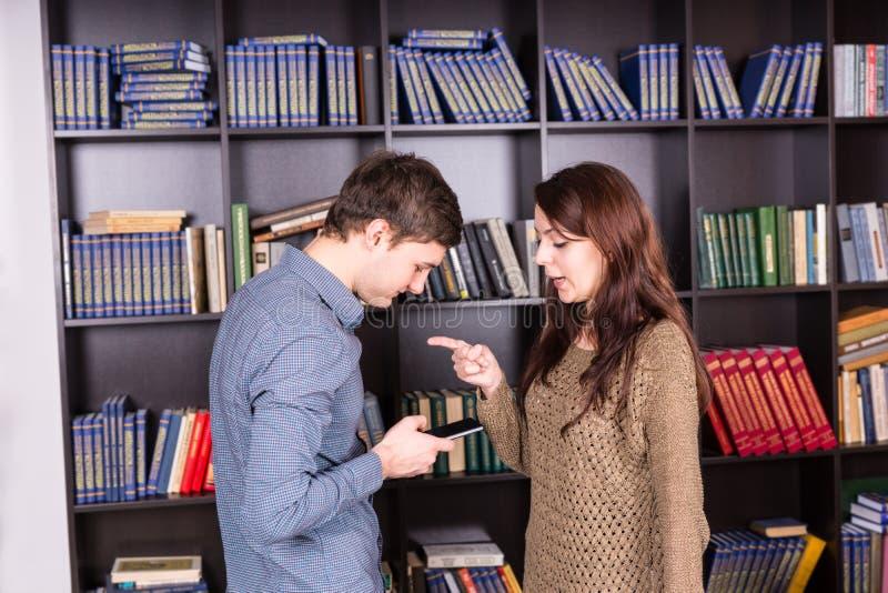 Женщина говоря его человеку чего к сообщению на телефоне стоковые изображения rf