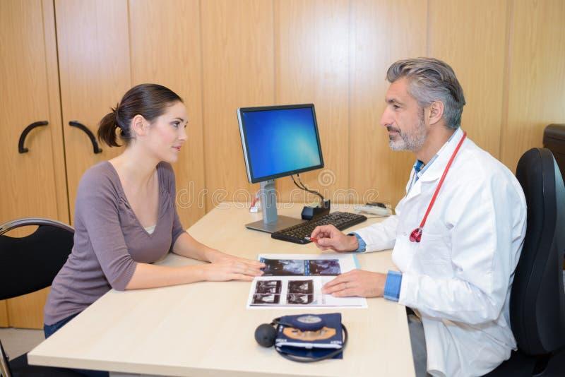 Женщина говоря к доктору стоковая фотография