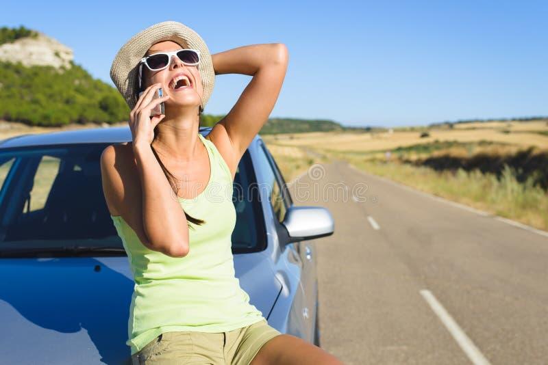 Женщина говоря на мобильном телефоне во время автомобильного путешествия лета стоковые фото