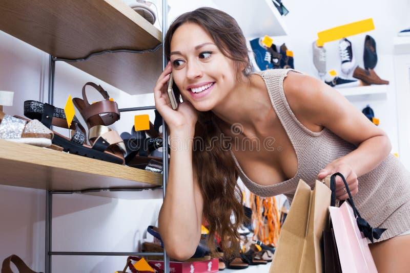 Женщина говоря на мобильном телефоне в магазине стоковое фото