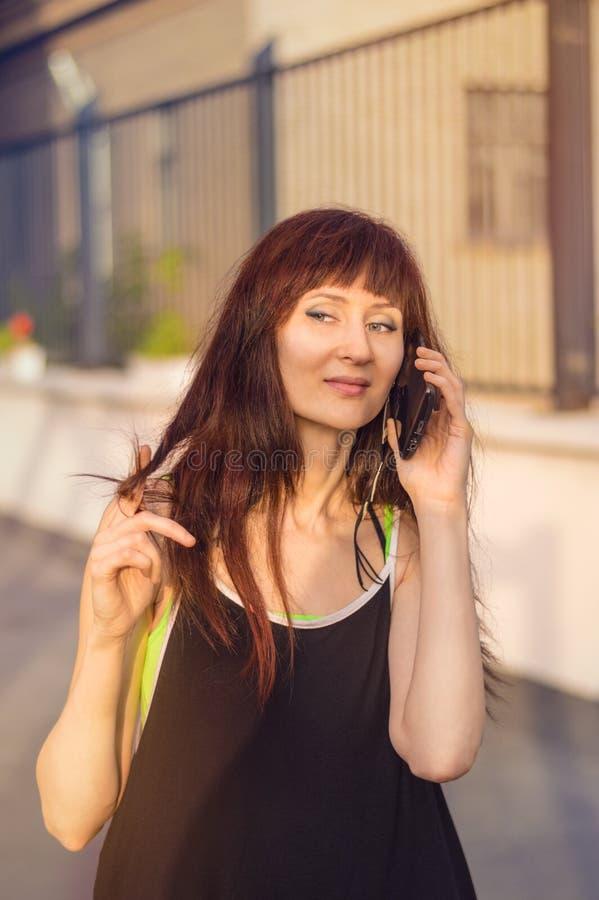 Женщина говоря на сотовом телефоне в streen стоковое изображение rf