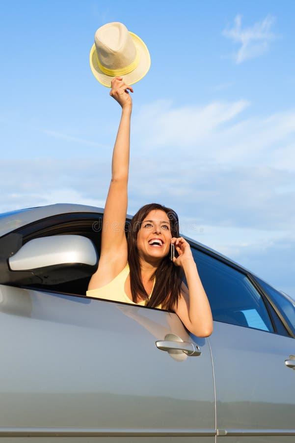Женщина говоря на телефоне и развевая от окна автомобиля стоковые фото
