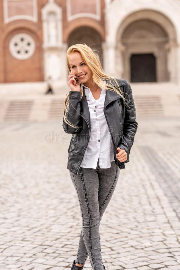 Женщина говоря по ее телефону пока стоящ на квадрате стоковая фотография rf