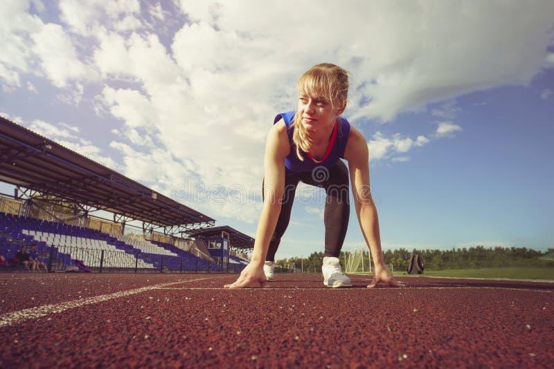 Женщина гонки подходящая уверенно в исходной позиции готовой для бежать Спортсменка около для того чтобы начать спринт посмотреть стоковое фото rf