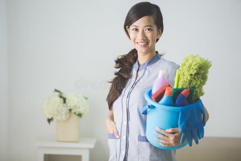 Женщина горничной чистки усмехаясь к камере стоковое фото rf