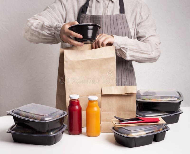 Женщина, готовящая одежду, складывая здоровую еду, едет стоковое фото rf