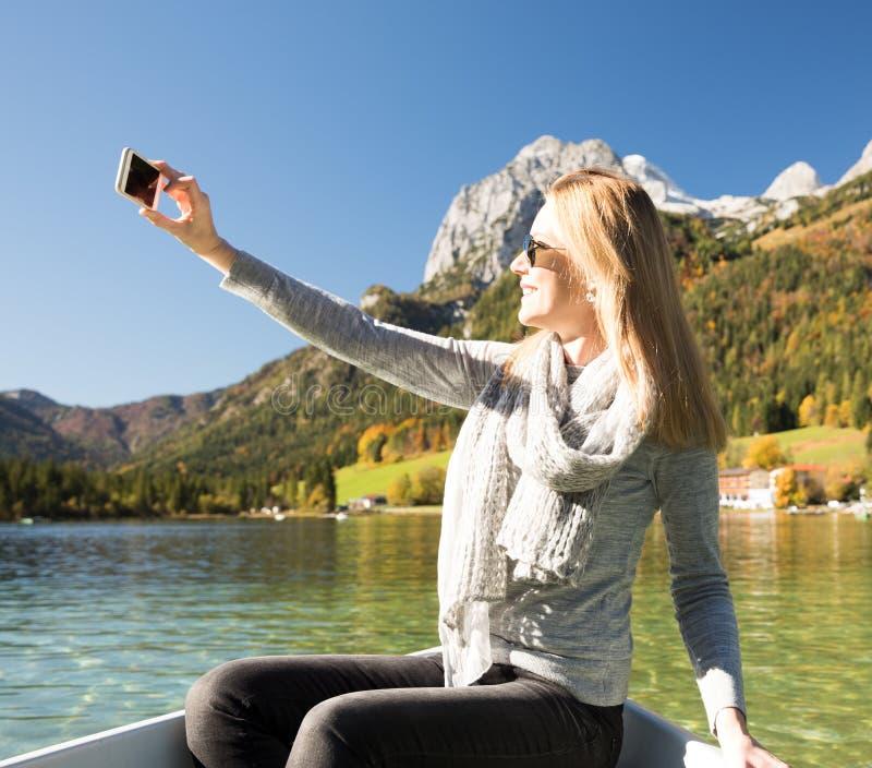 Женщина гребет с весельной лодкой с озером в горах стоковая фотография